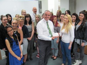 The group are pictured here presenting the cheque to John Logan, Volunteer with the charity at their tea party in Springburn Campus.