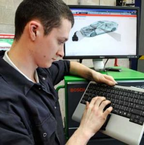 Student using technology to repair car
