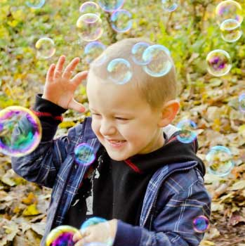 small boy playing with bubbles