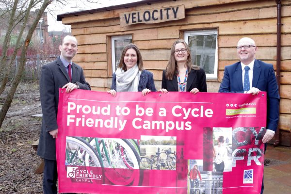 staff outside velocity holding banner