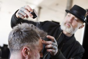 Barber putting product on clients hair