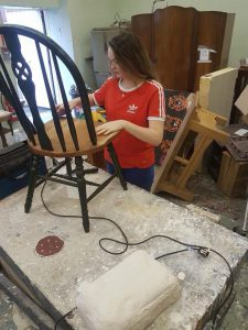 student restoring a chair