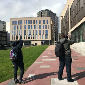 students taking photographs of building