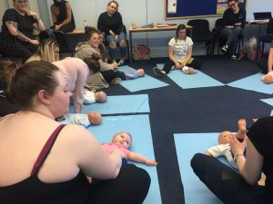 students with babies and dolls for baby yoga