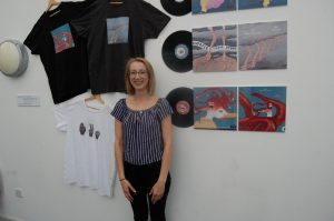 student with t-shirts and paintings