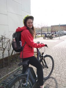 Female in red coat trying out e-bike