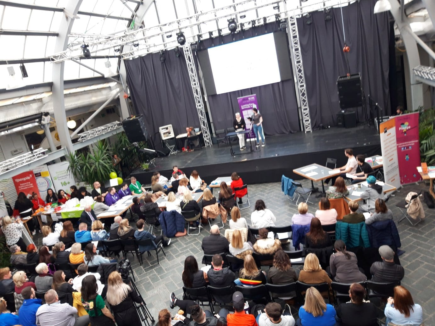 audience listening to speakers on stage