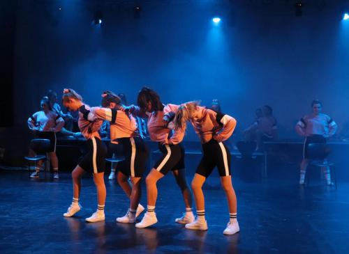 four dancers in a row, heads bowed