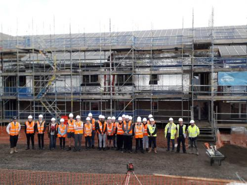 students in front of housing construction