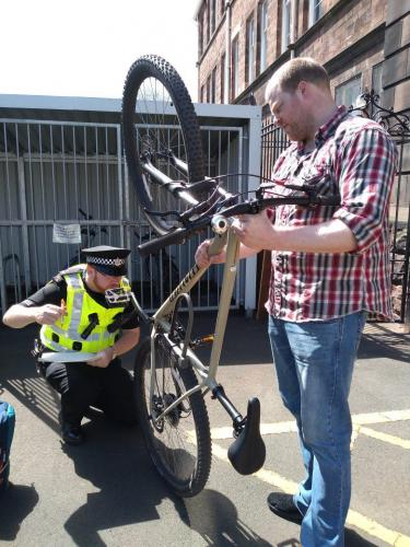 Technician working on bike with Policeman