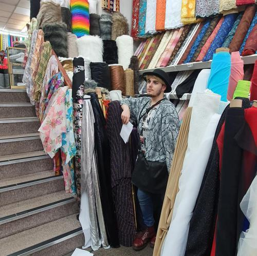 student standing beside rolls of fabric