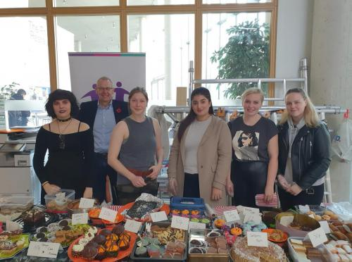 group shot of students and charity chairman at cake table