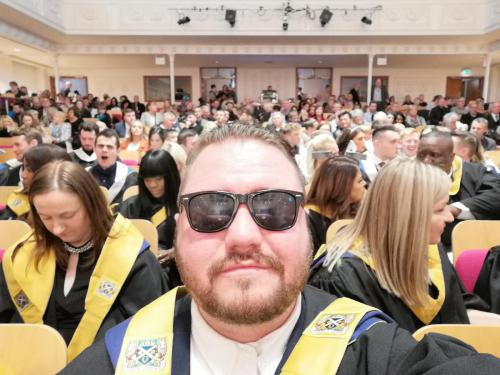 student selfie with other graduates behind him
