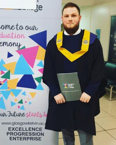 student in gown with certificate