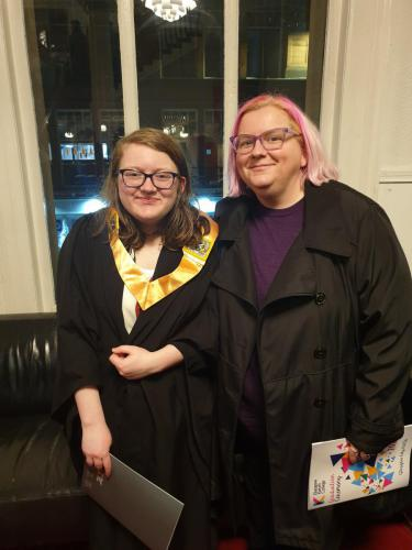 student in gown with guest