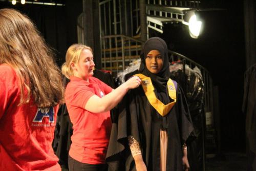 female student getting gown adjusted