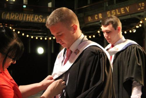 male student getting gown adjusted