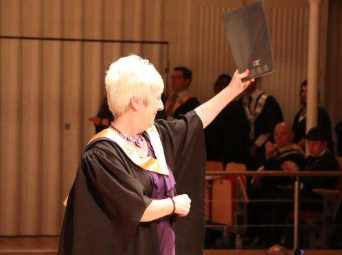 student holding up certificate