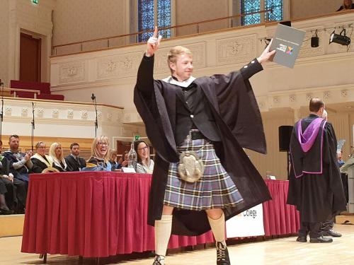 Student in kilt waving to audience