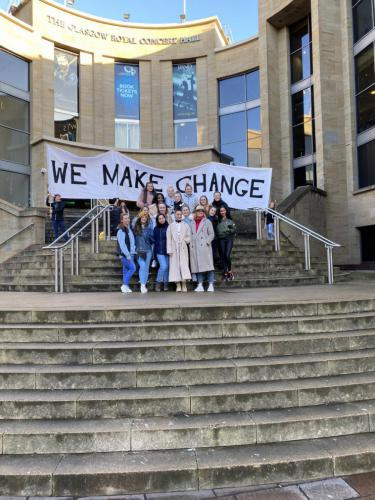 staff and students on stairs under We Make Change banner