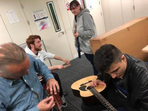 staff and students working on the guitars