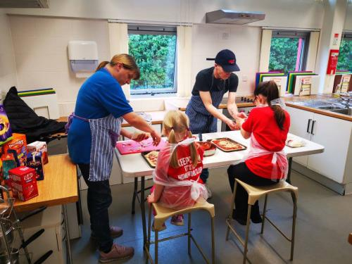 Adults helping children to bake