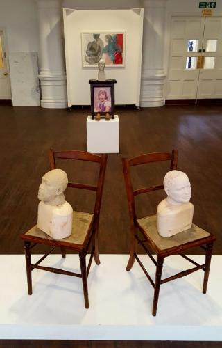 Two busts sitting on chairs with picture behind