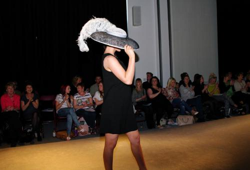 Millinery model in large feathered hat