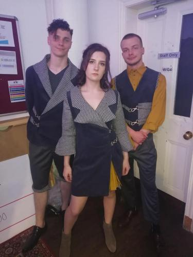 Three models in black and yellow outfits