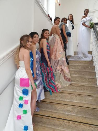 Models in long gowns on stairs, back view