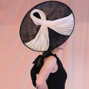 Model in large black and cream hat